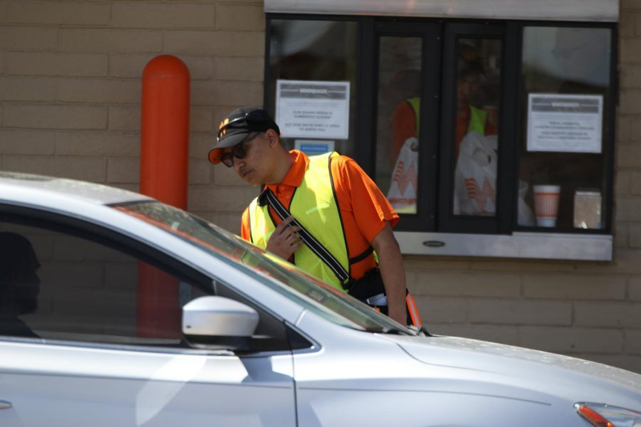 "(Working) At the Whataburger next to the school, Brian Heredia, 11, takes an order March 23 to help move the line faster. Despite the circumstances, this is a job he enjoys. ""I was kind of frustrated because there was a very long line of cars and sometimes it can be tricky to find the correct one and get it done quickly,"" Heredia said."